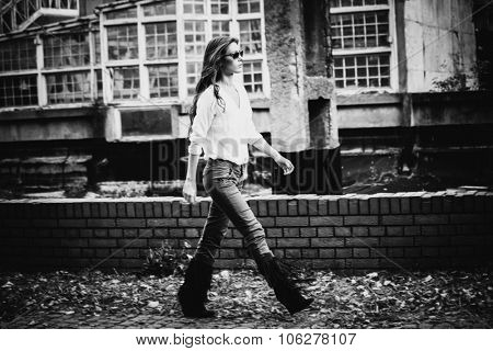 young woman in shirt,  tight pants and tassel boots, walk in front of old building, black and white, full body shot, small amount of grain added