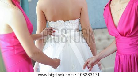 Two bride-maids in fuchsia dresses bustling the wedding dress. Bride-maids hands ribbon making