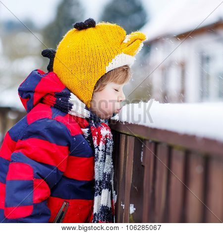 Little Kid Boy In Colorful Clothes Happy About Snow, Outdoors