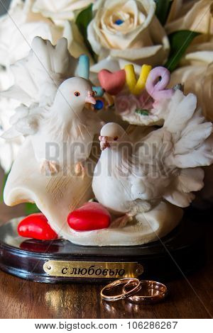 Two wedding rings lie the table.Figurine doves.Love.