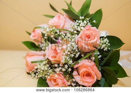 Two  wedding rings on a bouquet of pink roses