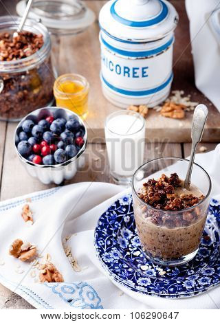 Oatmeal granola glazed with molasses and coffee, milk and fresh berries on a wooden background. Selective focus poster