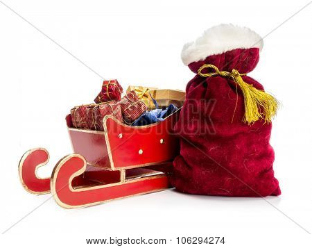 Red sleigh full of christmas presents and Santa Claus bag over white background