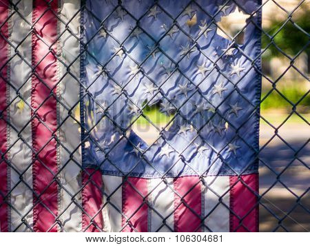 Tattered American flag hanging on chainlink fence