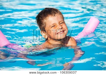 Close-up of boy learning to swim with pool noodle