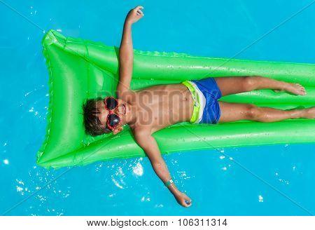 Boy wearing sunglasses relaxing on mattress