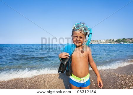 Boy with scuba mask and paddles on the seashore