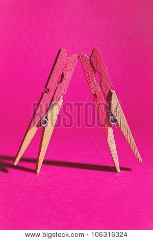 Pair Of Pink Painted Pegs Symbolising Females Leaning On Each Other