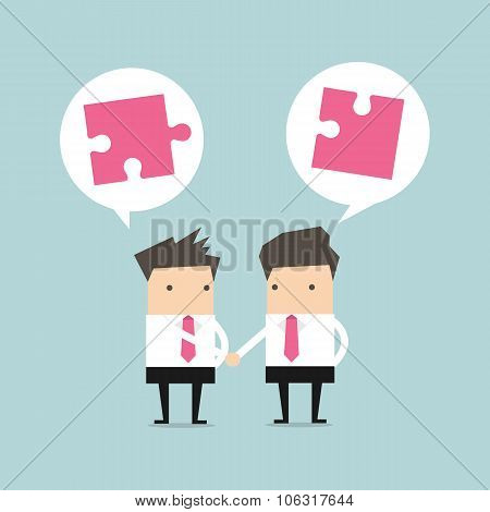 Businessman shaking hand with jigsaw conception
