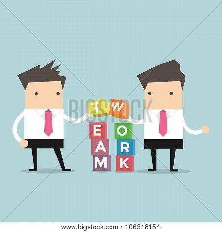 Two businessman is building Teamwork cubic box puzzle