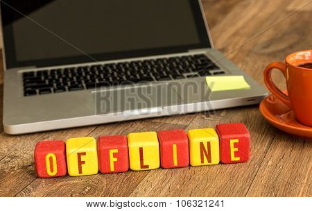 Offline written on a wooden cube in front of a laptop