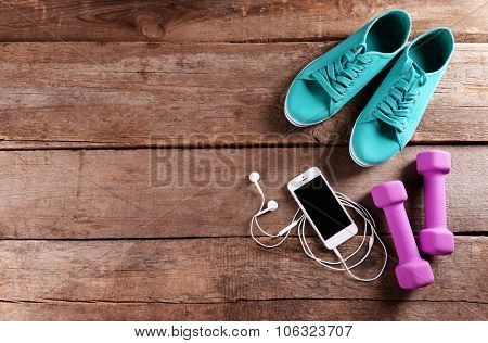 White cellphone with headphones and pink dumb bells and gumshoes on wooden background