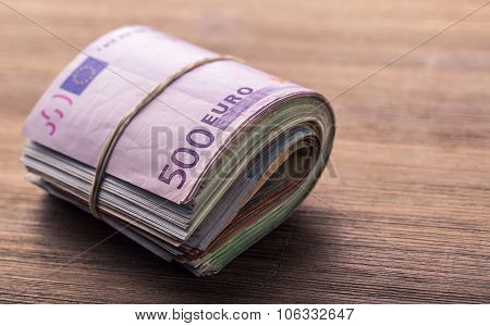 Euro money. Close-up Of A Rolled Euro Banknotes On Wooden table