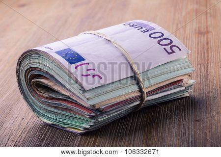 Euro currency. Euro money. Close-up Of A Rolled Euro Banknotes On Wooden table