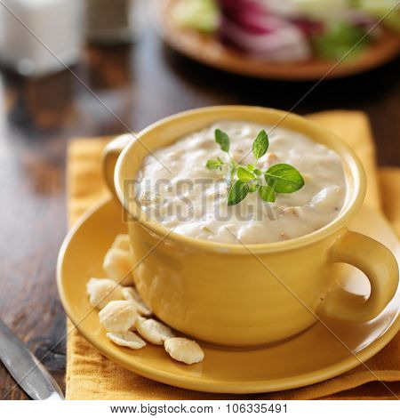 clam chowder in yellow bowl with cackers close up