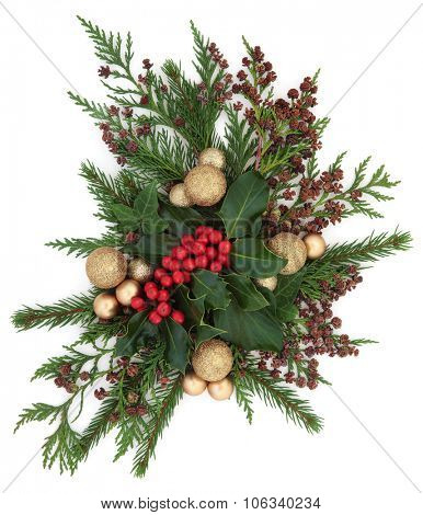 Christmas flora with gold bauble decorations, holly, ivy and winter greenery over white background.