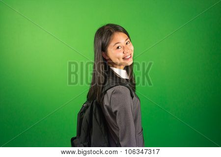 Portrait of a young and happy female student in green screen