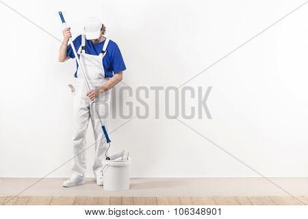 Painter Man At Work Takes Color With Paint Roller From The Bucket