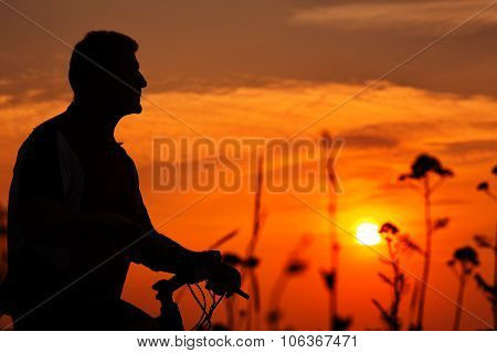 Silhouette of a man on muontain-bike