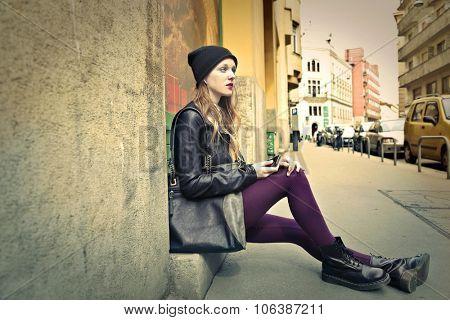 Urban girl sitting on the ground