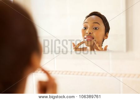 beautiful young african woman checking for pimple on her face