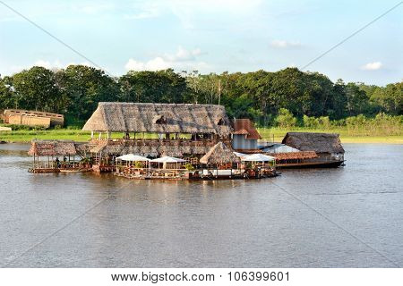 IQUITOS, PERU - OCTOBER 11, 2015: Al Frio y Al Fuego Floating Restaurant. The balsa raft restaurant on the Itaya River offers fine service and excellent Peruvian fusion cuisine and a floating pool.