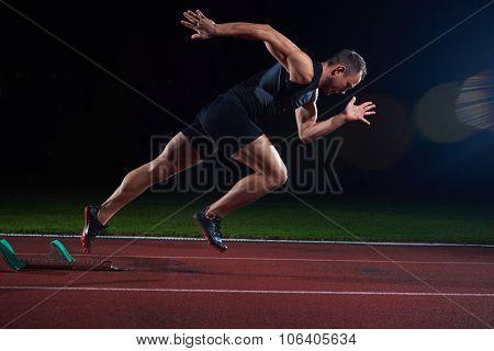 Sprinter leaving starting blocks on the running track. Explosive start. poster