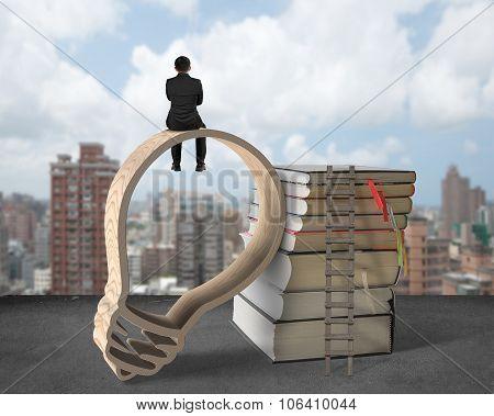 Businessman Sitting On Lightbulb Shape Wooden Frame With Books