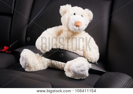Teddy bear fastened in the back seat of a car, safety on the road poster