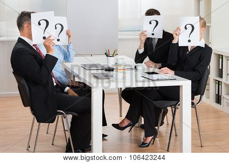 Businesspeople Hiding Faces Behind Question Mark Sign
