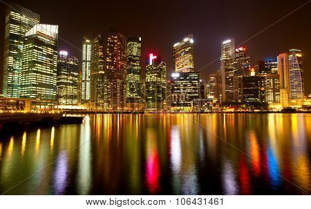 Panorama of modern skyscrapers Singapore at night time with water lite reflections.