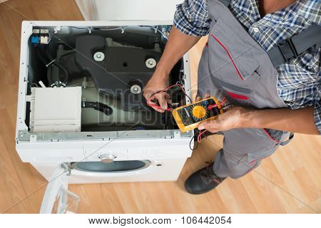 Technician Checking Washing Machine With Digital Multimeter