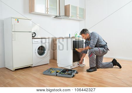 Technician Checking Dishwasher With Digital Multimeter