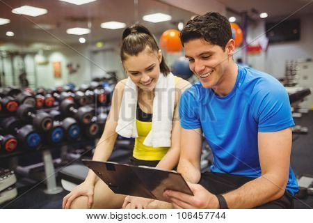 Trainer and client discussing her progress at the gym poster