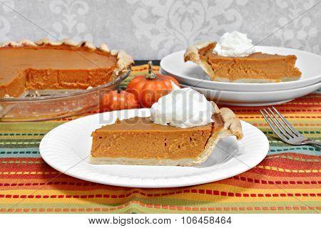 Pumpkin Pie Slice With Whole Pie In Background.