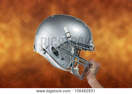 Close-up of American football player handing his sliver helmet against orange background