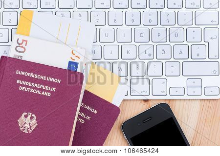 Airline tickets and travel passport of german over comuter keyboard poster
