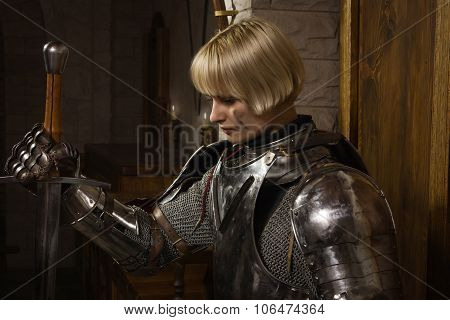 Joan of Arc. Girl in a knight's armor in the interior of a medieval castle poster