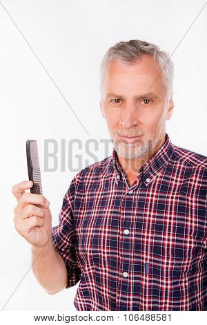 Confident aged man holding a comb on a white background poster