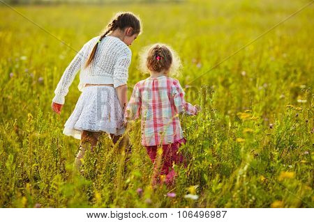 Little Girls Are Walking Among The Wildflowers