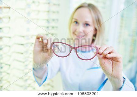 Female smiling optician seller holding eyeglasses. doctor optometrist at store  poster