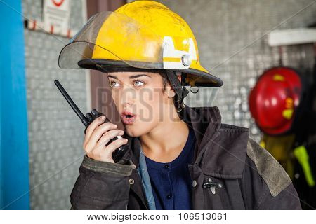 Confident young firewoman looking away while using walkie talkie at fire station