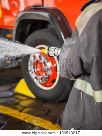 Midsection of firewoman spraying water while practicing at fire station