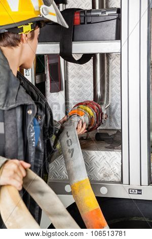 Young female firefighter fixing water hose in firetruck at station poster