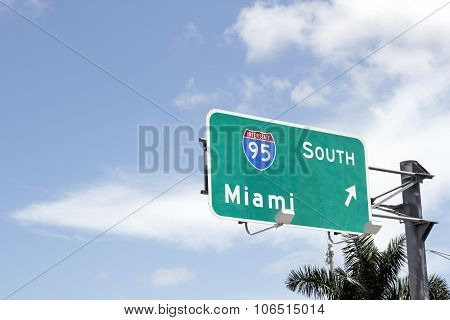 Large road sign signaling the way to go south to Miami on Interstate 95 in Florida. Behind the Interstate 95 South to Miami sign is blue sky with some white clouds and a palm tree on this sunny day. poster