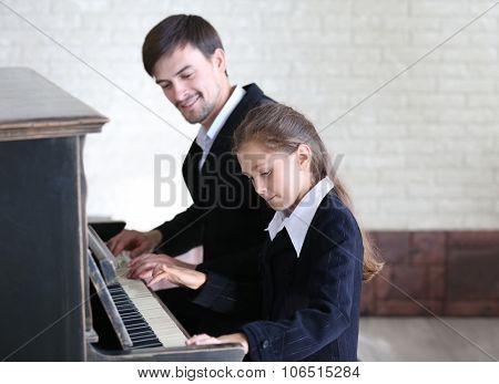 Musician teacher trains to play piano little girl