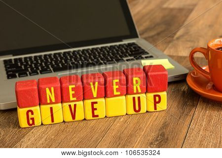 Never Give Up written on a wooden cube in front of a laptop