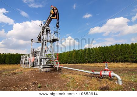 Grey oil pump jack on field and blue sky. poster