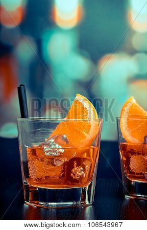 Glasses Of Spritz Aperitif Aperol Cocktail With Orange Slices And Ice Cubes On Bar Table, Pop Style