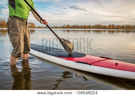 male paddler is starting  paddling workout on his stand up paddleboard on a lake in Colorado